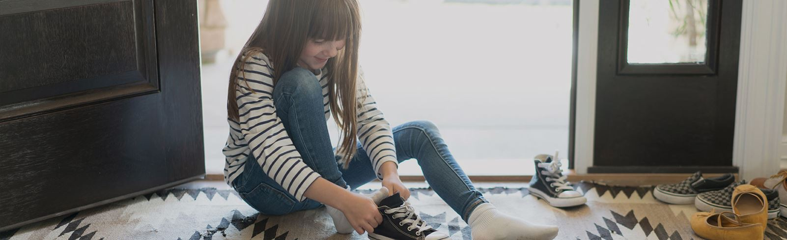 Little Girl Putting Shoes on in Her New Broomfield Colorado Home