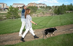 Couple walking dog on trails in Colorado master-planned community